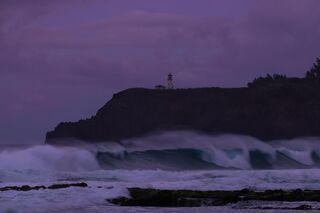 Big waves at Secret Beach, Kauai in Hawaii with Kilaulea lighthouse in the background.