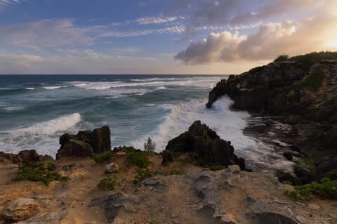 Overlook on the breaking waves and cliffs from Mahaulepu Heritage Trail near Shipwreck Beach on Kauai island in Hawaii.
