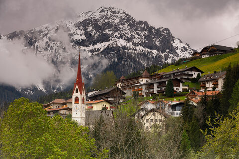 View on a small village and snow covered Mountain Peak in the Dolomites.