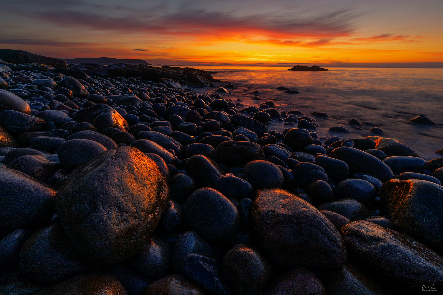 Colorful sunrise at Boulder Beach in Acadia National Park in Maine.