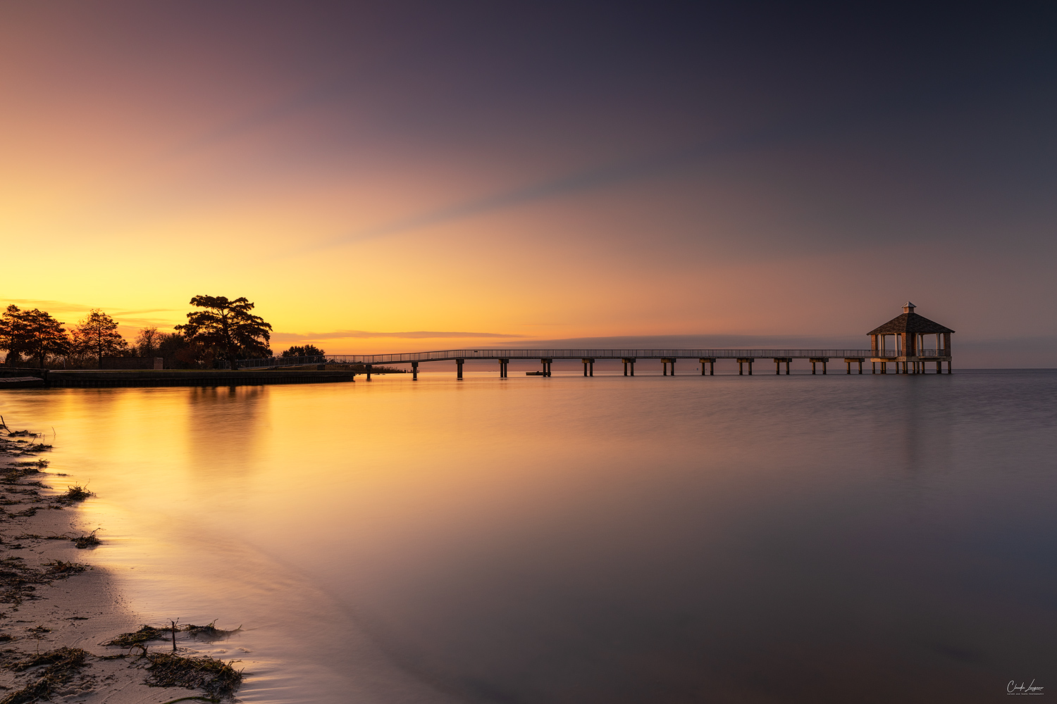 View of pier in Fontainebleu State Park in Louisiana at sunrise.