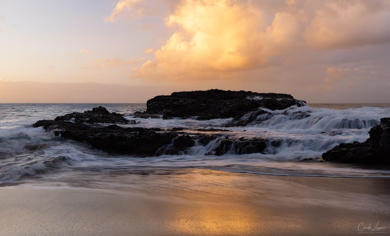 Waterfall cascades on black lava rock formation at Kahalahala Beach in Kauai island, Hawaii.