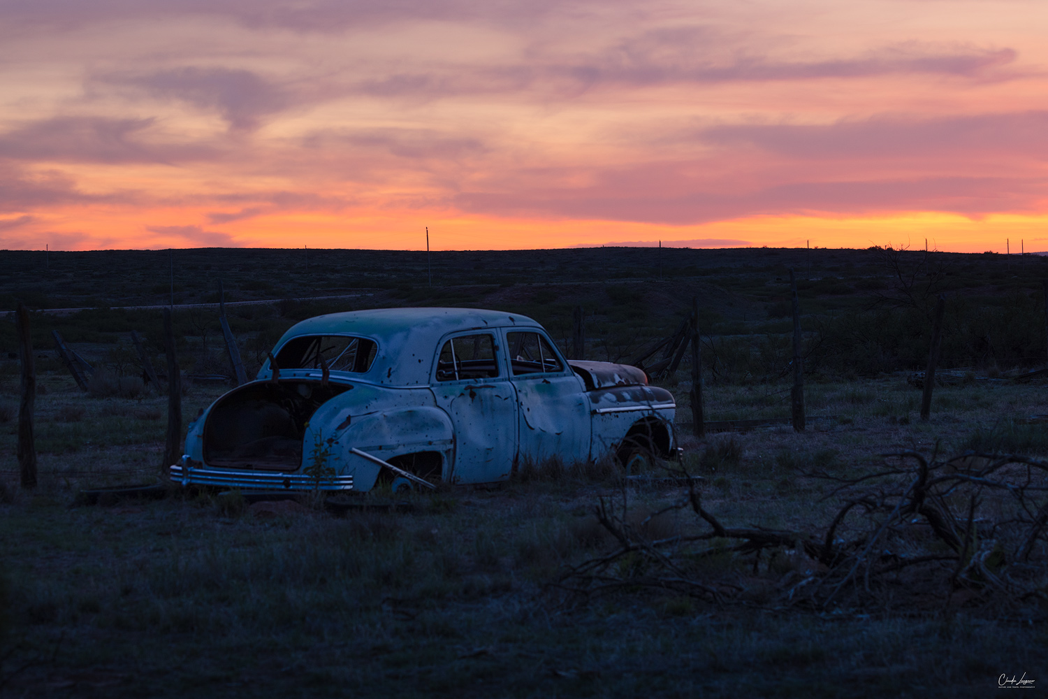 View of abandoned car in the ghost town of Endee in New Mexico at sunset.
