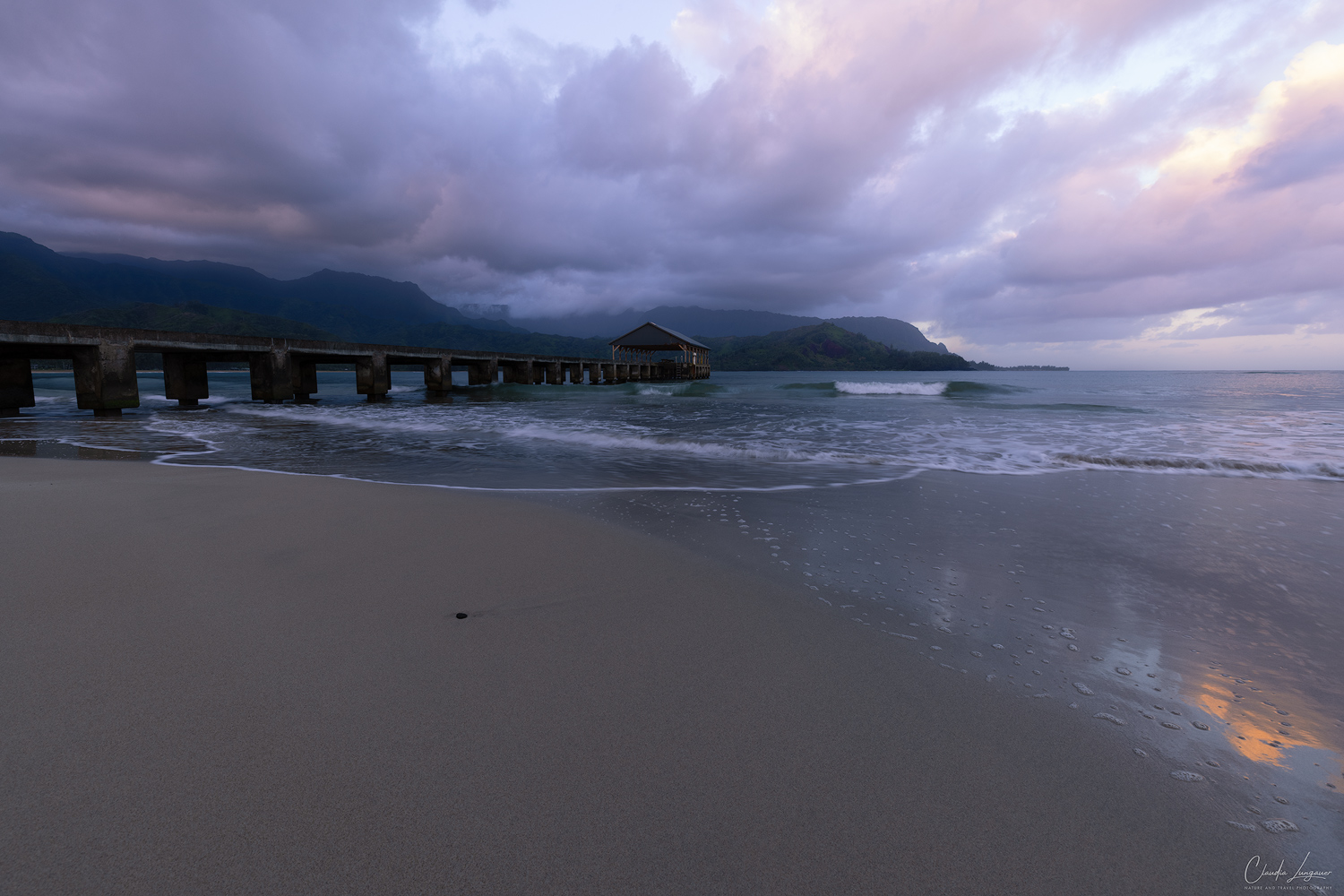 Dramatic clouds forming over Hanalei Pier and the rolling mountains on Kauai island in Hawaii.