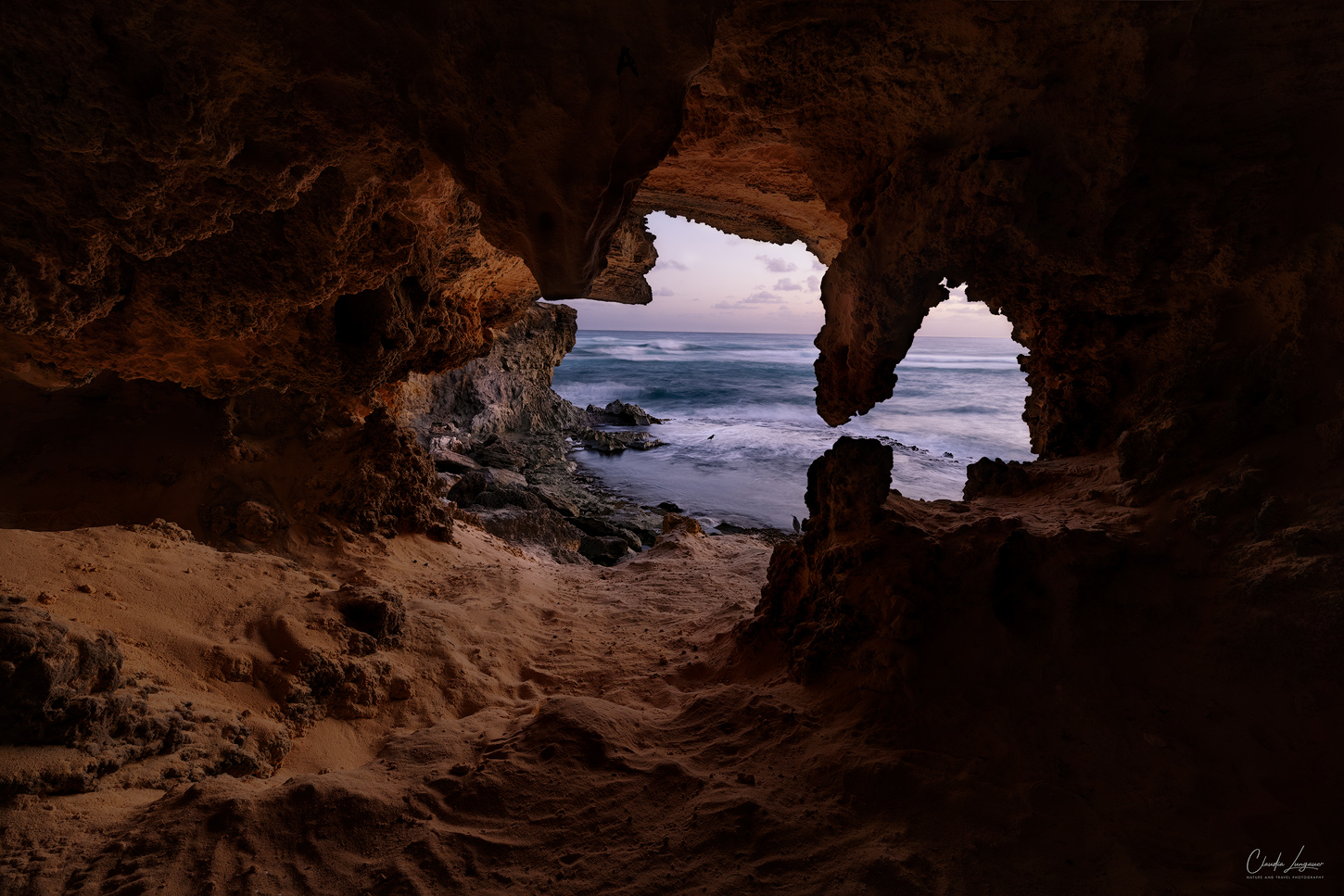 A cave near Shipwreck beach on the south shore of Kauai island in Hawaii with view on the Pacific Ocean.